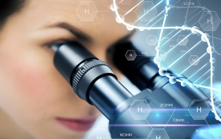 close up of scientist looking to microscope in lab